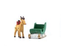 驯鹿和绿色雪橇白色背景 库存图片