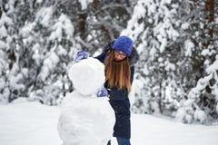 驱动乐趣爬犁冬天 一个被编织的帽子的女孩雕刻雪人 库存图片