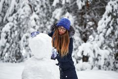 驱动乐趣爬犁冬天 一个被编织的帽子的女孩雕刻雪人 免版税库存照片