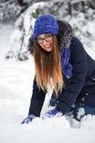 驱动乐趣爬犁冬天 一个被编织的帽子的女孩雕刻雪人 免版税库存图片