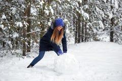 驱动乐趣爬犁冬天 一个被编织的帽子的女孩雕刻雪人 免版税图库摄影