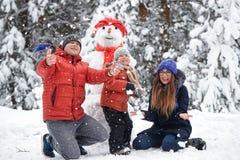 驱动乐趣爬犁冬天 女孩、做雪人的一个人和男孩 库存照片