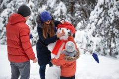 驱动乐趣爬犁冬天 女孩、做雪人的一个人和男孩 图库摄影