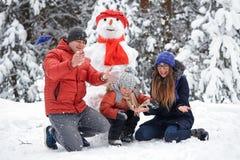 驱动乐趣爬犁冬天 女孩、做雪人的一个人和男孩 免版税图库摄影