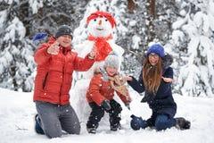 驱动乐趣爬犁冬天 女孩、做雪人的一个人和男孩 免版税库存图片