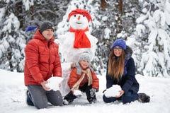 驱动乐趣爬犁冬天 女孩、做雪人的一个人和男孩 库存图片