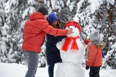 驱动乐趣爬犁冬天 女孩、做雪人的一个人和男孩 免版税库存照片