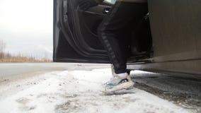 驱动冬天 在路的一个汽车身分 年轻人走向汽车并且得到里面 股票录像