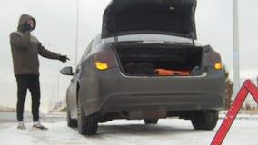 驱动冬天 汽车麻烦 一个紧急标志 在一条多雪的乡下公路的汽车麻烦 年轻人叫急救工作 股票录像