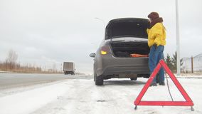 驱动冬天 汽车麻烦 一个紧急标志 在一条多雪的乡下公路的汽车麻烦 年轻女人电话抢救 股票视频