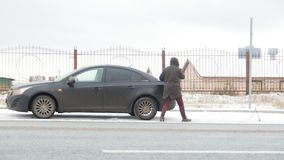 驱动冬天 汽车麻烦 一混乱的年轻人离开汽车并且走到树干 影视素材