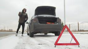 驱动冬天 汽车麻烦 在一条多雪的乡下公路的汽车麻烦 年轻人从汽车走出去 股票视频