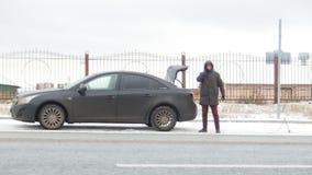 驱动冬天 汽车麻烦 搜查在树干的一混乱的年轻人 股票录像