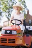 驱动割草机户外微笑的妇女 免版税库存照片