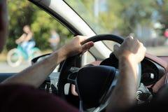 驱动器 人的手方向盘的 人拿着在一辆现代汽车的方向盘的司机在背景的  免版税库存照片