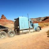 驱动在沙漠间的半卡车 库存图片