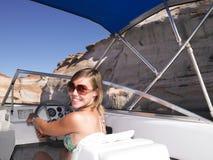 驱动微笑的妇女年轻人的小船 免版税库存照片