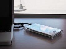 驱动被连接到在一张木书桌上的一台笔记本计算机 保留信息的概念在贸易 免版税图库摄影