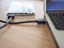 驱动被连接到在一张木书桌上的一台笔记本计算机 保留信息的概念在贸易 免版税库存照片