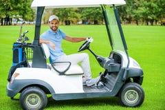 驱动高尔夫球人的购物车 免版税库存图片