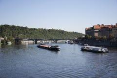 驳船和拖轮航行在伏尔塔瓦河河的货船和河巡航在查理大桥附近 免版税库存照片