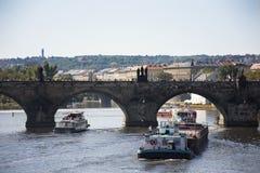 驳船和拖轮航行在伏尔塔瓦河河的货船和河巡航在查理大桥附近 库存照片