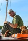 驾游艇者旅行与他的在一条老风船的狗 图库摄影