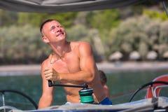 驾游艇者转动在帆船的绞盘绳索控制风帆 体育运动 免版税库存图片