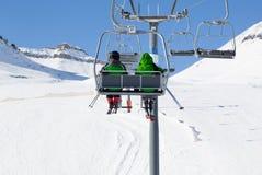 驾空滑车和雪滑雪倾斜的两个滑雪者 免版税库存照片