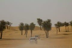 驾车到徒步旅行队在打击在迪拜,阿拉伯联合酋长国的沙丘以后野营 库存图片
