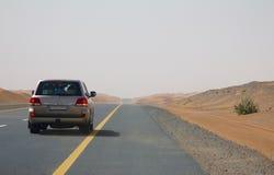 驾车在一条空的路在迪拜,阿拉伯联合酋长国的沙漠 免版税图库摄影
