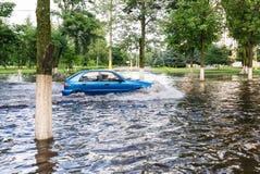 驾车在一条被充斥的路在大雨造成的洪水期间 免版税库存图片