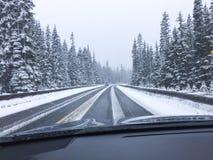 驾车在冬天雪的积雪的多雪的山路 司机` s看通过挡风玻璃的观点观点 库存图片