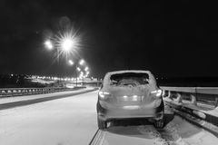驾车在多雪的天气的一条积雪的路在晚上 库存图片