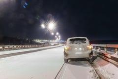 驾车在多雪的天气的一条积雪的路在晚上 图库摄影