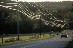驾车在有输电线的一条路下在日落期间在惠洛克,佛蒙特 免版税库存图片