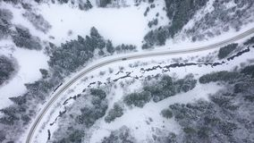 驾车的鸟瞰图沿冬天森林之前围拢的路 影视素材