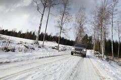 驾车路多雪的suv 免版税库存图片