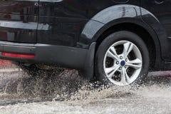 驾车通过在一条被充斥的路的一个水坑用水和飞溅导致由大雨 免版税库存图片