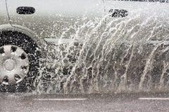 驾车通过在一条被充斥的路的一个水坑用水和飞溅导致由大雨 图库摄影