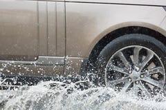 驾车通过在一条被充斥的路的一个水坑用水和飞溅导致由大雨 免版税库存照片