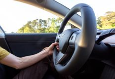 驾驶一个新的特斯拉模型3的人 库存照片