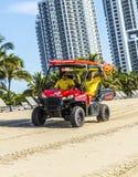 驾驶一个海滩儿童车的救生员在迈阿密海滩 图库摄影