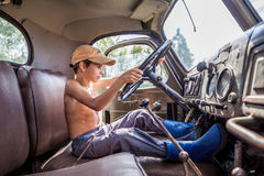 驾驶一辆大卡车的小男孩在夏天 图库摄影