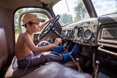 驾驶一辆大卡车的小男孩在夏天 库存照片