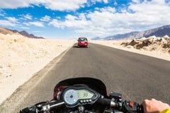 驾驶一辆摩托车的骑自行车的人在拉达克  库存照片
