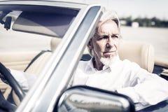 驾驶一辆敞篷车经典汽车的老人 免版税库存照片
