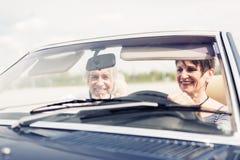 驾驶一辆敞篷车经典汽车的资深夫妇 免版税库存图片