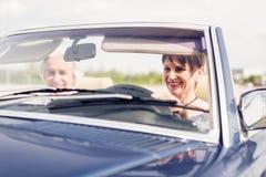 驾驶一辆敞篷车经典汽车的资深夫妇 库存照片