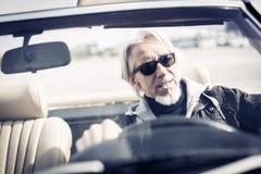 驾驶一辆敞篷车经典汽车的老人 免版税库存图片